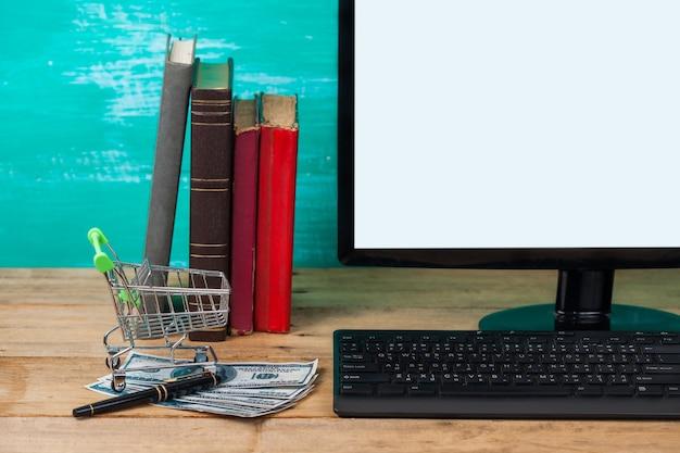 Panier et argent avec ordinateur à la maison sur le bureau Photo Premium