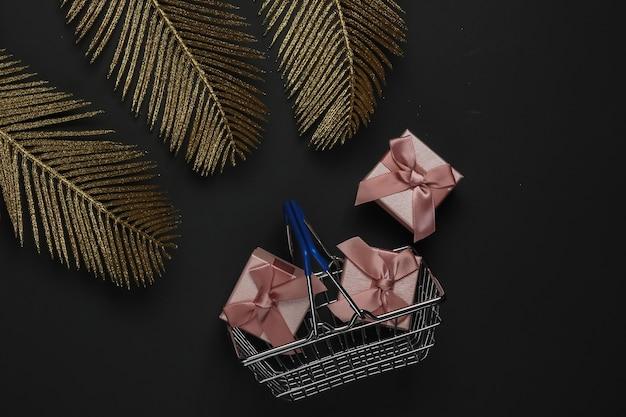Panier Avec Boîte-cadeau Sur Fond Noir Avec Des Feuilles De Palmier Dorées. Mise à Plat De La Mode. Vendredi Noir. Vue De Dessus Photo Premium