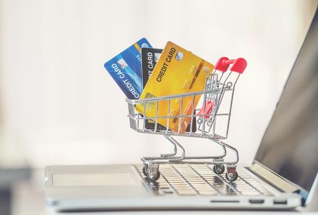 Panier et carte de crédit avec ordinateur portable sur le bureau Photo Premium