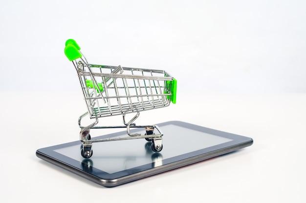 Panier ou chariot en métal sur tablette mobile pour les achats en ligne et le commerce électronique. Photo Premium