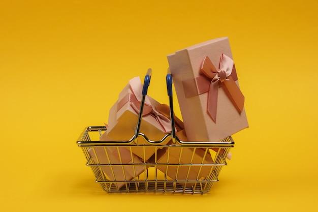 Panier Et Coffrets Cadeaux Avec Des Arcs Sur Fond Jaune. Composition Pour Noël, Anniversaire Ou Mariage. Photo Premium