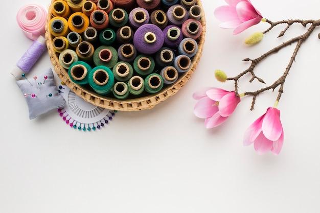 Panier avec des fils à coudre et des fleurs d'orchidées naturelles Photo gratuit