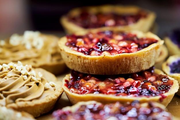 Panier à Gâteau Avec Des Fruits Recouverts De Gelée Sur La Vitrine D'une Pâtisserie. Fermer Photo Premium