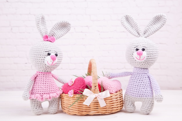 Panier en osier avec des coeurs tricotés multicolores. lapin tricoté. décor de fête. la saint valentin. jouet tricoté à la main, amigurumi Photo Premium
