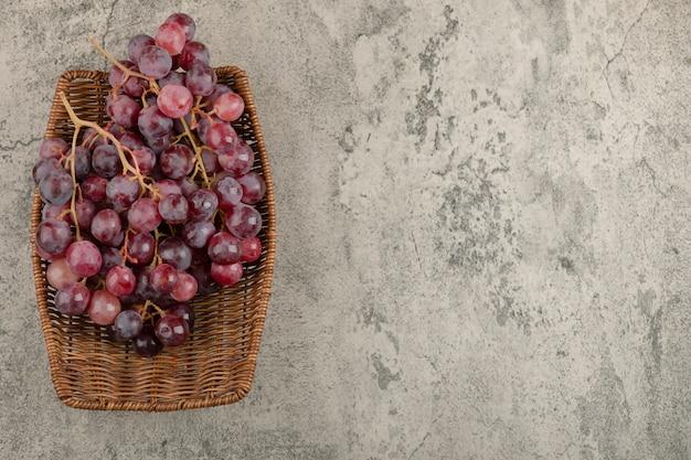 Panier En Osier De Délicieux Raisins Rouges Sur Table En Marbre. Photo gratuit