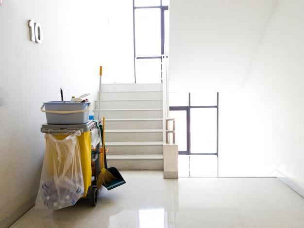 Le panier d'outils de nettoyage attend le nettoyeur.seau et équipement de nettoyage au bureau. Photo Premium