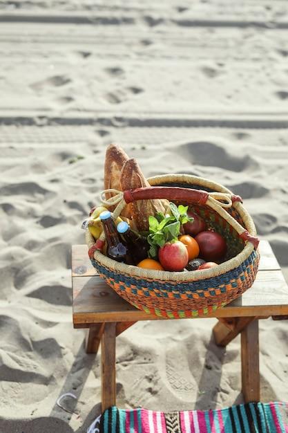 Panier de pique-nique rempli de collations et de boissons à la plage Photo Premium