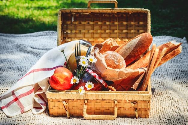 Panier De Pique-nique Rempli De Fruits, Pain Et Pot Avec De La Confiture D'abricot Photo Premium
