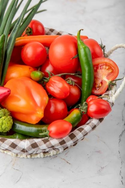 Panier Plein De Légumes Comme Des Tomates, Des Poivrons Et Des Oignons Verts Sur Une Surface Blanche Photo gratuit