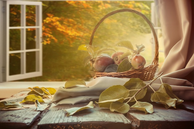 Panier de pommes, livre à carreaux, table de coupe près d'une fenêtre donnant sur le paysage d'automne, automne Photo Premium
