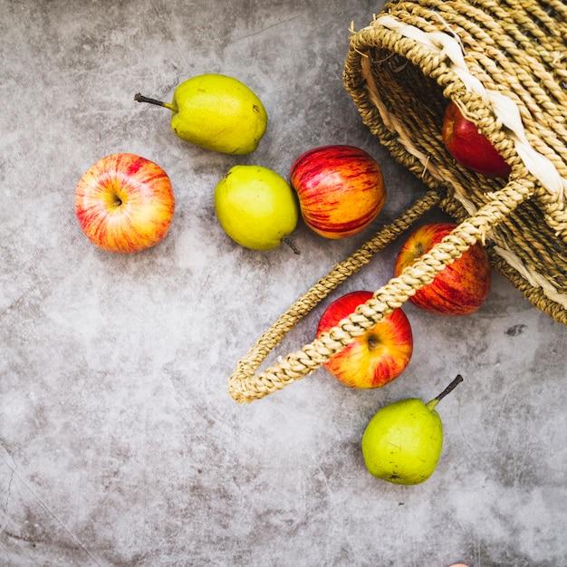 Panier avec des pommes qui tombent Photo gratuit