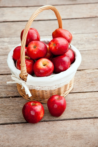 Panier de pommes rouges sur plancher de bois Photo Premium