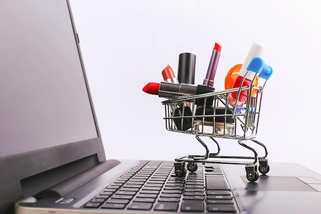 Le panier avec les produits de beauté est sur l'ordinateur portable. concept de vente en ligne. Photo Premium