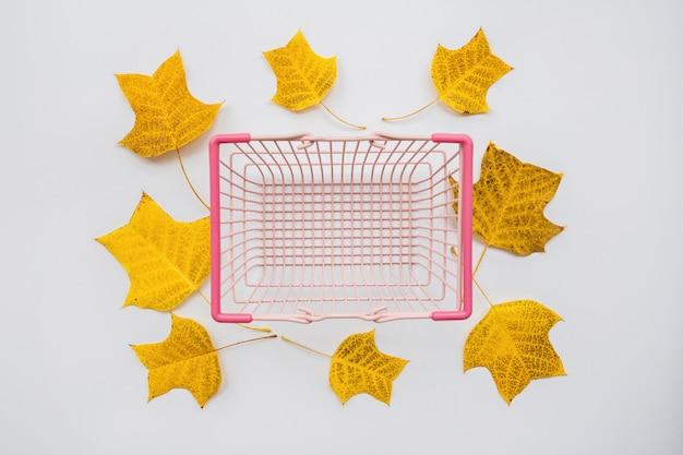 Panier à provisions et feuilles d'automne sur fond blanc Photo Premium