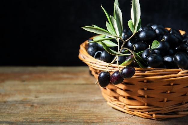 Un Panier De Wiker Plein D'olives Noires Fraîches Et Mûres Des Pouilles, En Italie, Discret Photo Premium