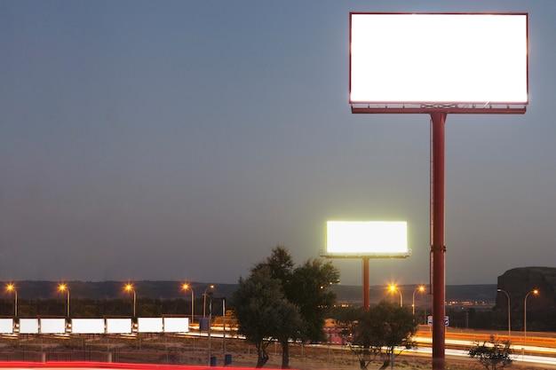 Panneau d'affichage blanc blanc sur la route éclairée pendant la nuit Photo gratuit