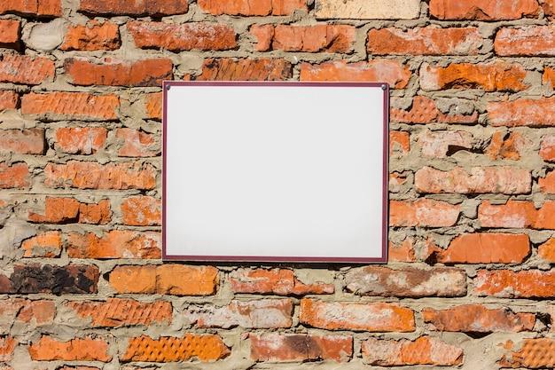 Panneau d'affichage blanc vierge sur le vieux mur de brique orange. maquette. Photo Premium