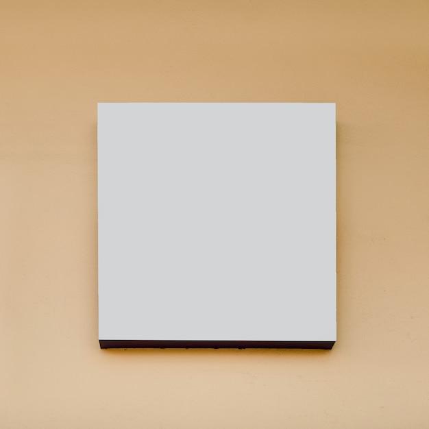 Panneau d'affichage de forme carrée blanc sur fond beige Photo gratuit