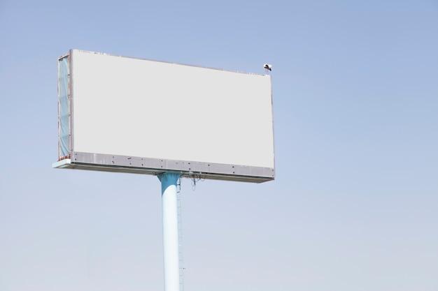 Panneau d'affichage pour la publicité contre le ciel bleu Photo gratuit