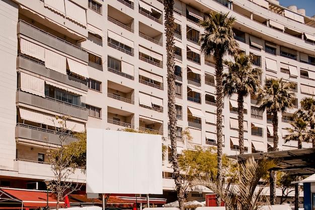 Panneau d'affichage publicitaire devant l'immeuble d'habitation Photo gratuit
