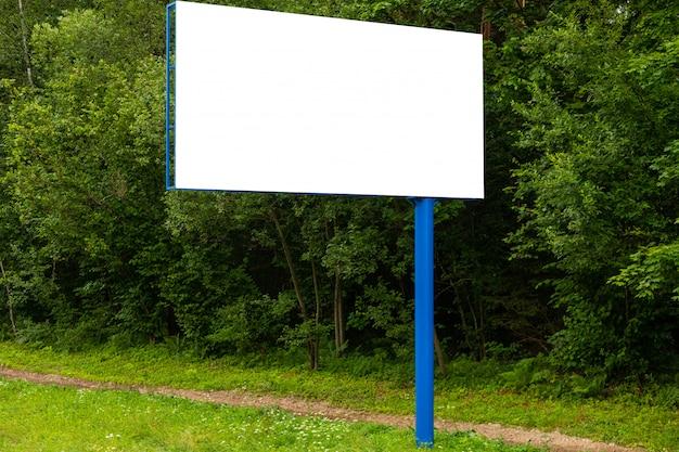 Panneau D'affichage Vide Blanc Contre La Forêt Verte Le Long De La Route Photo Premium