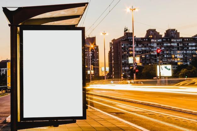Panneau D'affichage Vide Dans L'arrêt De Bus La Nuit Avec Les Lumières Des Voitures Qui Passent Photo Premium