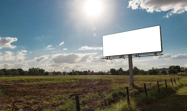 Panneau d'affichage vide en face de beau ciel nuageux dans une zone rurale Photo Premium