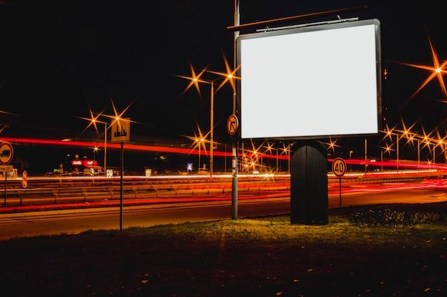 Panneau d'affichage vide avec des feux de circulation floues dans la nuit Photo gratuit