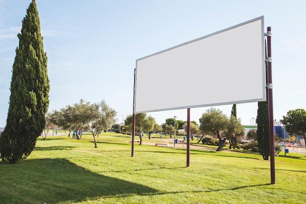 Panneau d'affichage vide pour la publicité sur l'herbe verte dans le jardin Photo gratuit