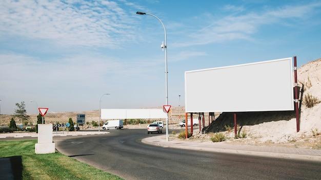 Panneau d'affichage vide près de la route courbe Photo gratuit