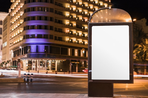 Panneau d'affichage vide de publicité dans la ville illuminée Photo gratuit