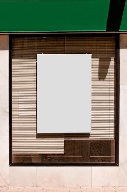 Panneau d'affichage vide rectangulaire sur la fenêtre en verre avec des stores Photo gratuit