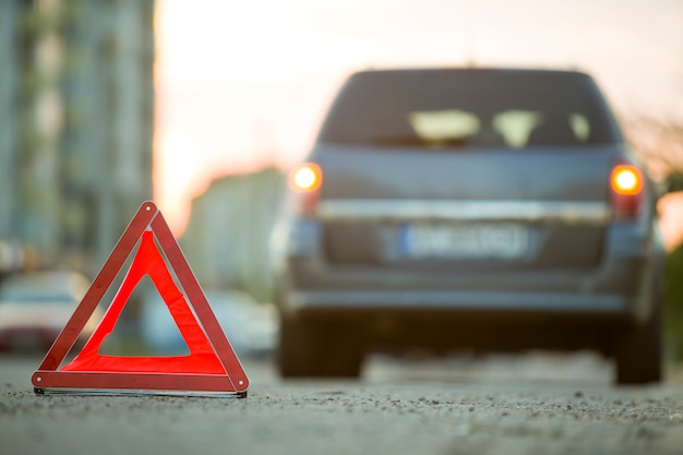 Panneau d'arrêt triangle rouge d'urgence et voiture cassée dans une rue de la ville. Photo Premium