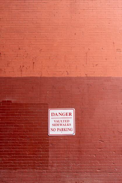 Panneau d'avertissement sur la vue de face du mur de briques Photo gratuit