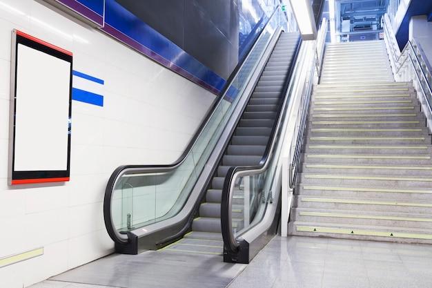 Un Panneau Blanc Vide Sur Le Mur Près De L'escalator Et De L'escalier Photo gratuit