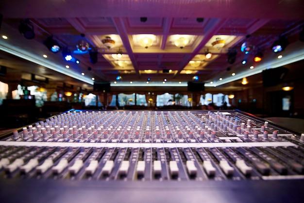 Panneau de contrôle professionnel dj sur une salle de fête d'arrière-plan flou. Photo Premium