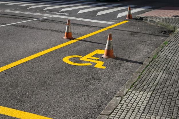 Panneau de fauteuil roulant juste peint sur la route pour marquer une place de stationnement pour les personnes handicapées. Photo Premium