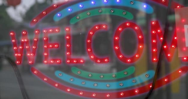 Panneau lumineux avec des lumières rouges avec inscription bienvenue sur la porte vitrée Photo Premium