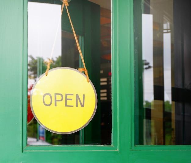 Panneau ouvert jaune suspendu au café porte en bois Photo Premium