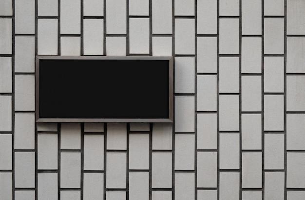 Panneau de signalisation vierge noir sur la texture du mur Photo Premium