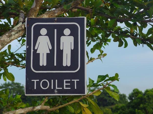 Panneau de toilette suspendu à un arbre à feuilles vertes dans le parc public extérieur. Photo Premium