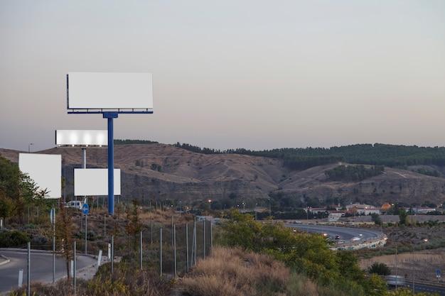 Panneaux d'affichage blancs sur l'autoroute avec les montagnes en arrière-plan Photo gratuit