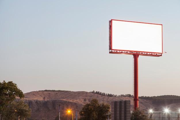 Panneaux d'affichage vierges pour la publicité extérieure près des montagnes Photo gratuit