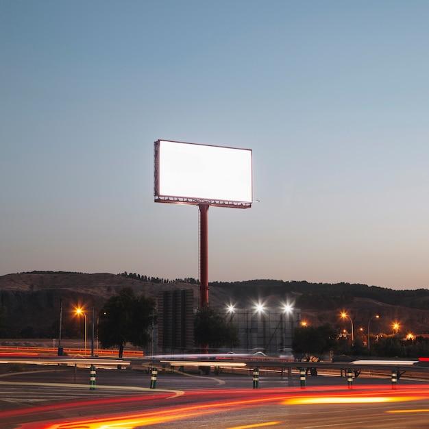 Panneaux publicitaires vierges sur la route éclairée la nuit Photo gratuit
