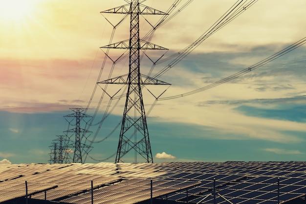 Panneaux solaires avec pylône électrique et coucher de soleil. concept d'énergie propre Photo Premium