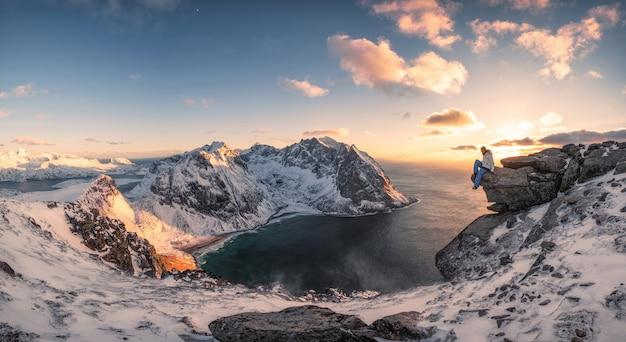 Panorama de l'alpiniste assis sur un rocher au sommet d'une montagne de la côte arctique au coucher du soleil Photo Premium