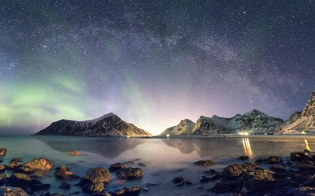 Panorama d'aurora borealis avec la voie lactée sur une montagne enneigée sur le littoral Photo Premium