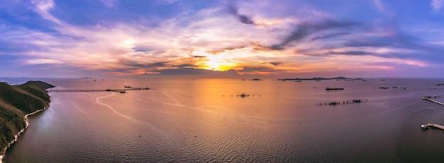 Panorama crépuscule paysage ciel bleu la montagne de la mer et la station d'expédition huile aérienne haut Photo Premium