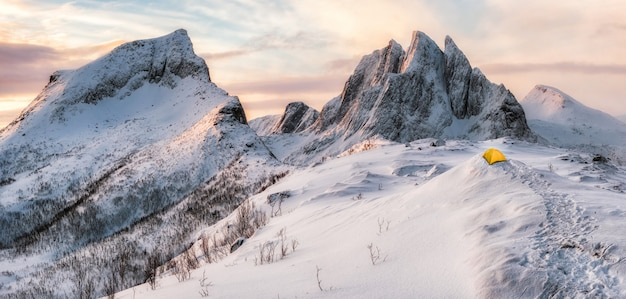 Panorama des montagnes escarpées avec neige couverte et tente jaune Photo Premium