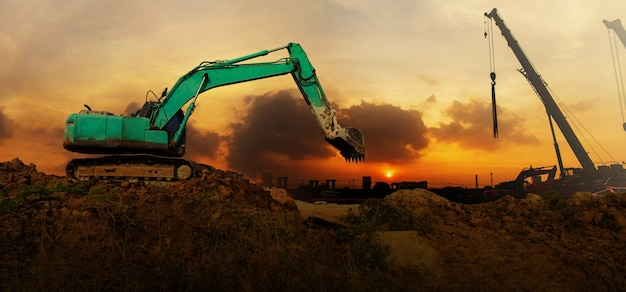 Panorama de la pelle travaillant sur un chantier de construction au coucher du soleil Photo Premium
